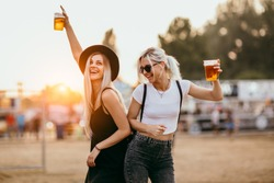 Two female friends drinking beer and having fun at music festival