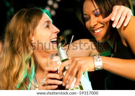 Two female friends having drinks in a bar or nightclub