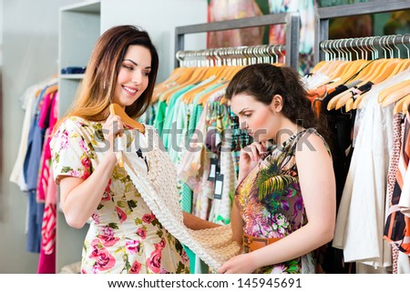 Two female friends having fun while fashion shopping in boutique or store