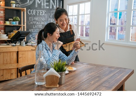 two female friends in coffee shop chatting and discussing on social media with mobile phone. waitress in apron served lady regular customer and gossip with her looking together on smartphone screen.