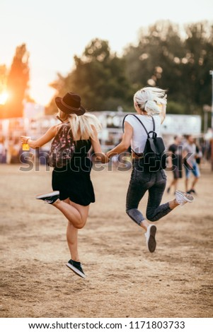 Two female friends jumping and having fun at music festival. Back view #1171803733