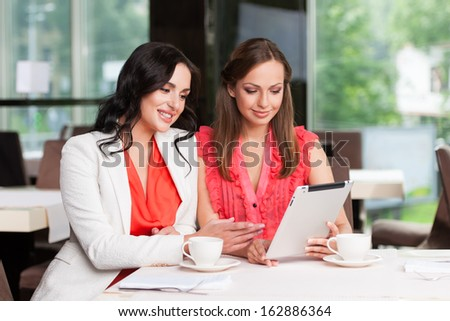 Two female friends looking at ipad Smiling and looking happy