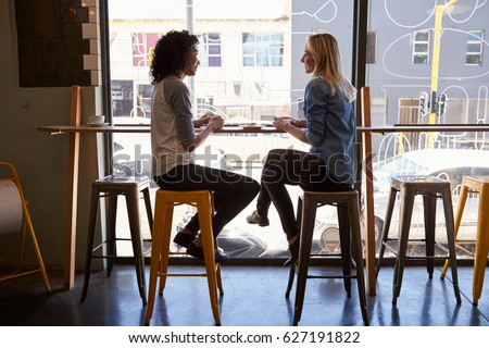 Two Female Friends Meeting In Coffee Shop