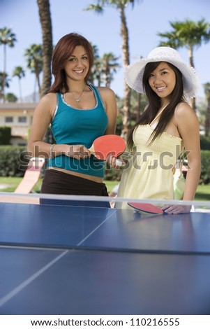 Two female friends playing table tennis