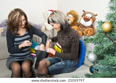Two female friends preparing Christmas presents on a sofa.