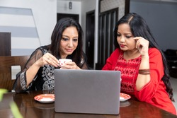 Two female friends sitting at home with laptop infront of them, holding tea cup and looking into computer.