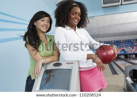 Two female friends smiling at the bowling club