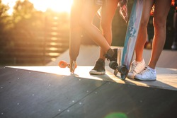 Two female friends standing with skateboards at the skate park.Only legs and boards are visible.Sunset.