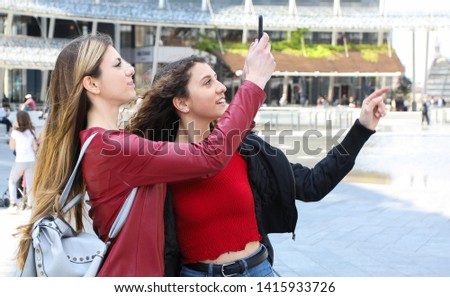 Two female friends taking pics while walking in a modern city