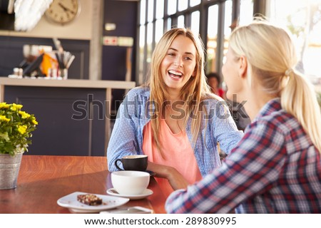 Two female friends talking at a coffee shop Stock photo ©