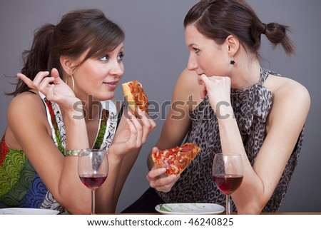 two female friends talking in studio with glasses sparkling wine and pizzas