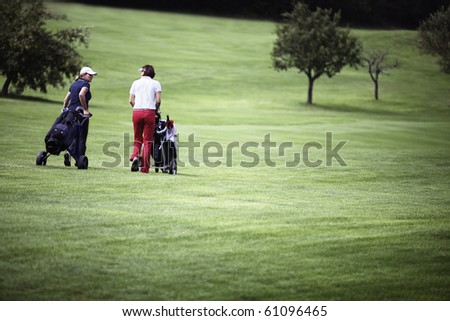 Two female golf player walking on fairway with their golf trolleys, plenty of copy-space. - stock photo
