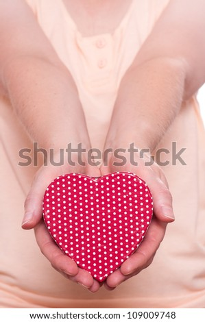Two female hands are holding a red heart ahead
