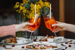 Two female hands cheers by glasses with a cocktail at the table