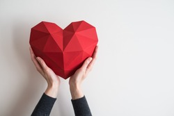 Two female hands holding red polygonal paper heart shape