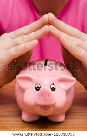 Two female hands over a pink piggy bank