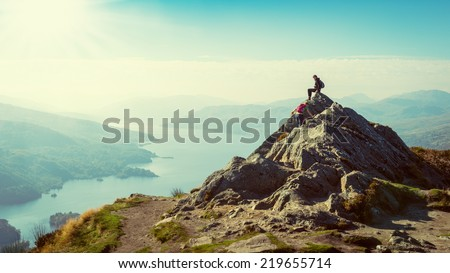 Two female hikers on top of the mountain enjoying valley view, Ben A'an, Loch Katrina, Highlands, Scotland, UK #219655714