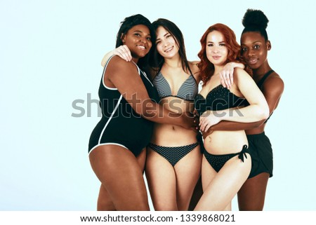 Two female interracial homosexual couple standing in sports underwear isolated over white studio background. Love, friendship, women beauty concept