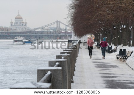Two female joggers in the Gorky Park. And view at Moscow River, Krymsky Bridge and Cathedral of Christ the Saviour. Moscow, Russia. #1285988056