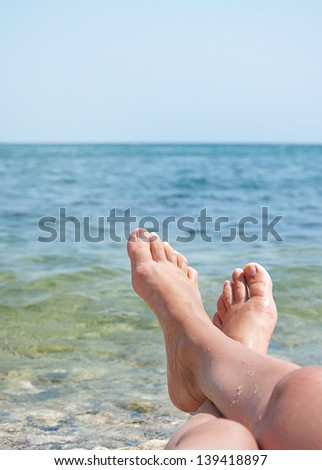 two female legs on beach over sea waves and blue sky