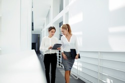 Two female managing directors discussing ideas of project on digital tablet while walking down in office hall, confident women entrepreneurs working on touch pad while going to the conference room