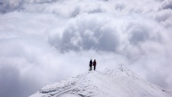two female mountain climbers on a narrow summit ridge high above cloud banks in the valleys below