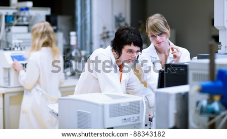 two female researchers/chemistry students doing research in a chemistry lab (color toned image; shallow DOF)