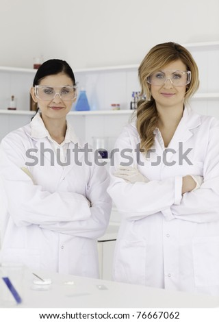 Two female scientists looking at the camera while standing in a lab