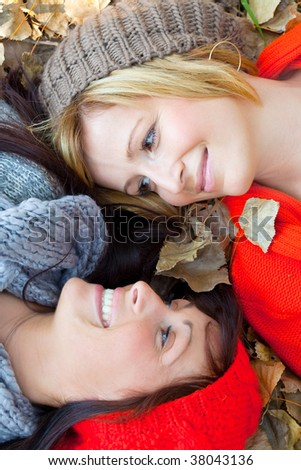 Two female sister girls lying in a lot of autumn fall leaves smiling eachother wearing winter clothes