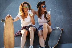 Two female skaters friends sitting on ramp at the skate park and drinking juice .Laughing and fun.
