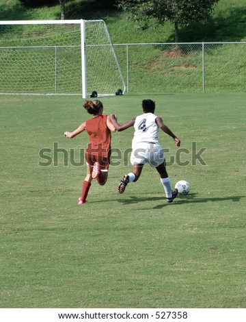Two female soccer players fight for the ball