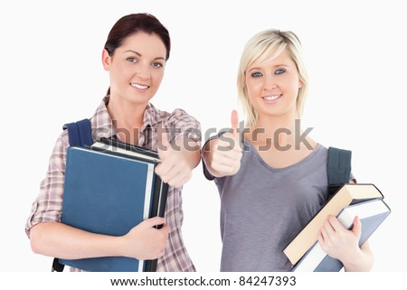 Two female students with books and thumbs up