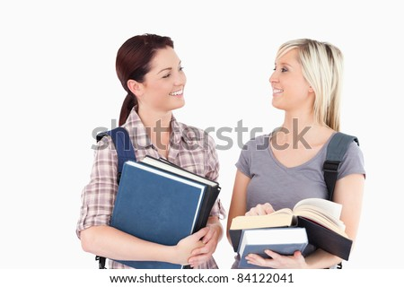Two female students with books looking at each other - stock photo