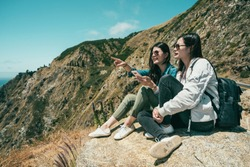 two female tourists finding something by the phone and one girl is pointing somewhere ahead while sitting on the cliff.