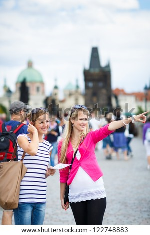 Two female tourists walking along the Charles Bridge while sightseeing in Prague, the historical capital of the Czech Republic (color toned image; shallow DOF)