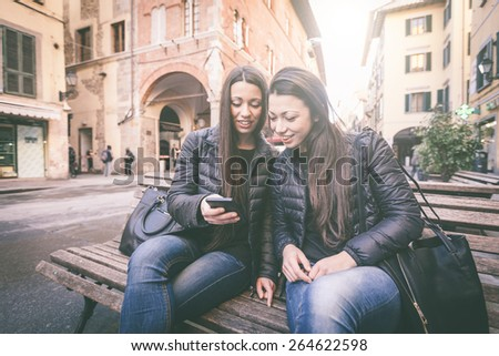 Two female twins looking at a smart phone. They wear black jackets and jeans. Urban scene with houses and street on background.