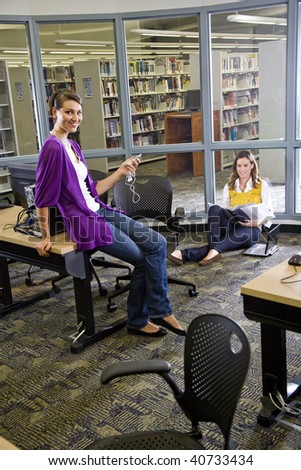 Two female university students studying in library