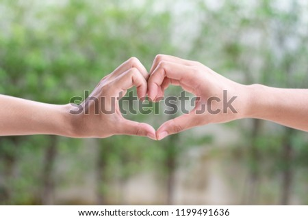 Two female woman hands in the form of heart symbol love on green  background. #1199491636