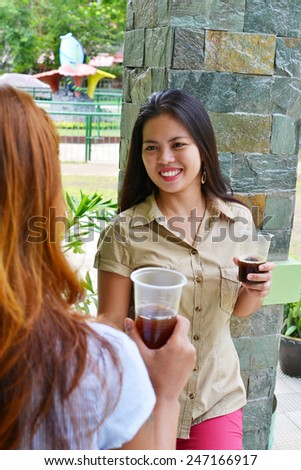 Two female workers having a funny conversation during a coffee break in the installations of the company