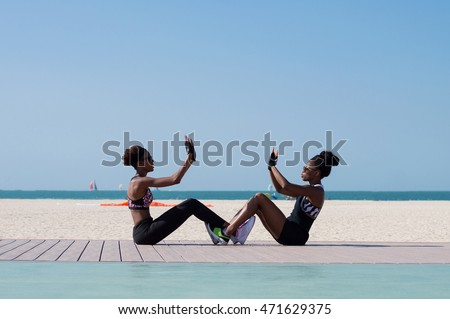 Two females of african ethnicity sitting at the seaside and doing sport exercises together at Dubai beach, UAE