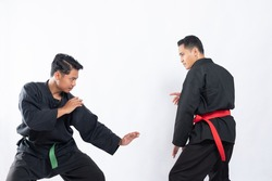 two fighters in pencak silat Hitam uniform fight in low stance and side stance movements on an isolated background
