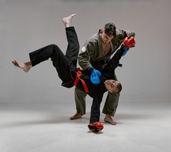 Two fighting guys in kimono and boxing gloves during battle, knockout, martial arts, mixed fight concept