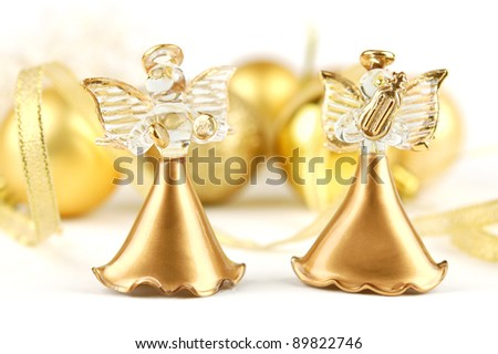 Two figurine of angels on the background of Christmas ornaments