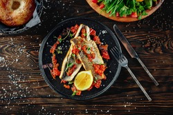 Two fillets of seabass with rich garlic and tomato sauce. Served hot on the black plate with cutlery on the side of the plate. Wooden table