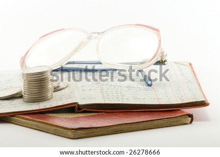 two financial ledgers with a pair of spectacles and a pile of coins on a white background