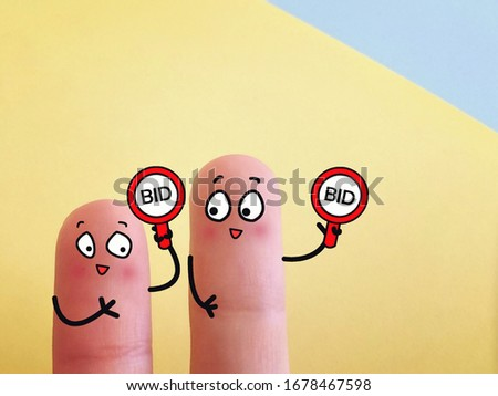 Two fingers are decorated as two person. Both of them are in an auction.
