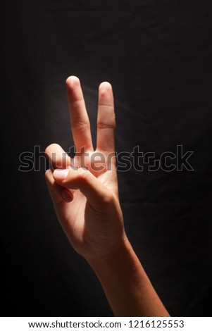 Two fingers, index finger and middle finger. Man hand victory isolated on black background.