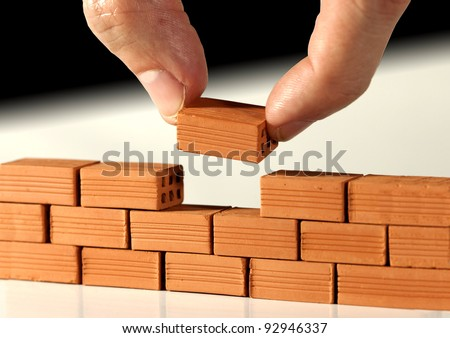 Two fingers put the last brick on the wall. Metaphoric scene #92946337