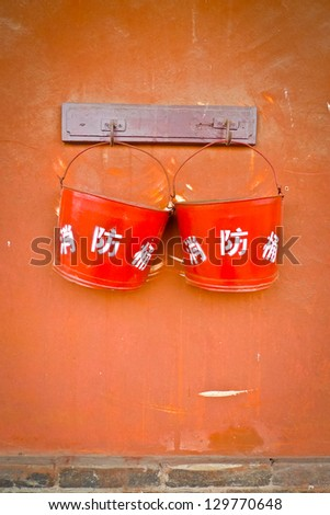 Two fire buckets hung on a brown wall in Pingyao, China