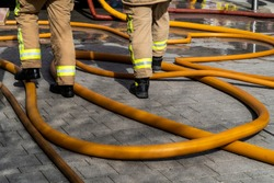 Two fire fighters in uniform stand among bright yellow orange fire hoses coiled across grey paved precinct. Wide bore pumped high pressure water used to extinguish fires. A trip hazard on the floor.